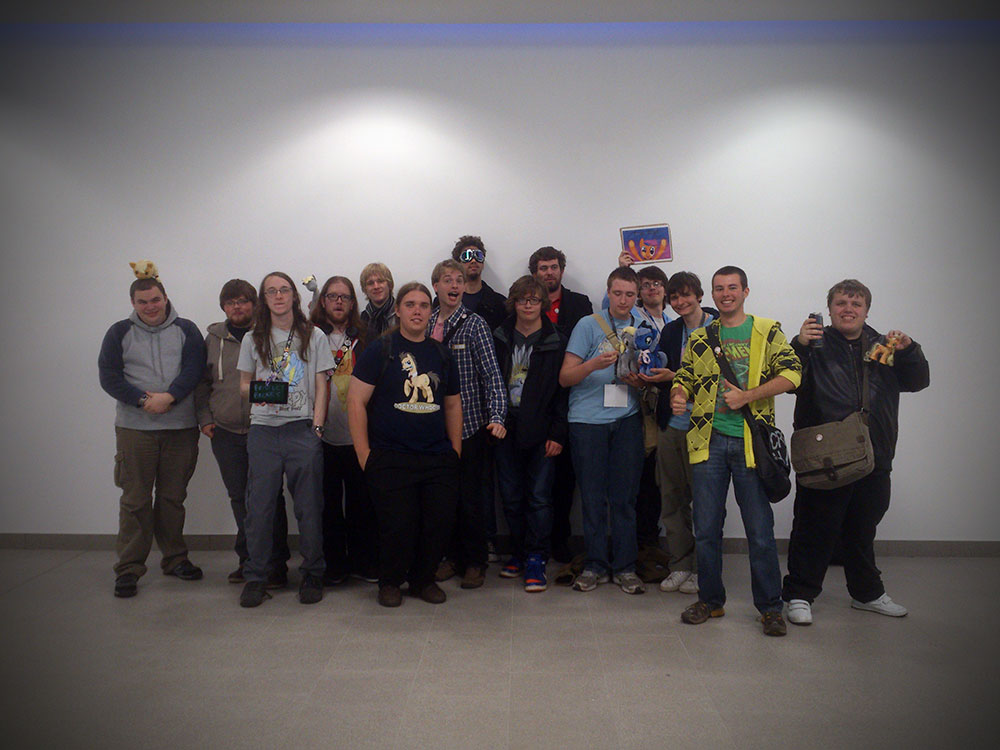A group of 15 bronies pose in front of a plain white wall.
