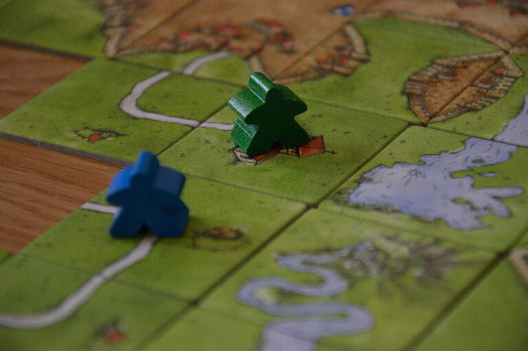 A close up photo of blue and green meeples on top of tiles from the game Carcassone.