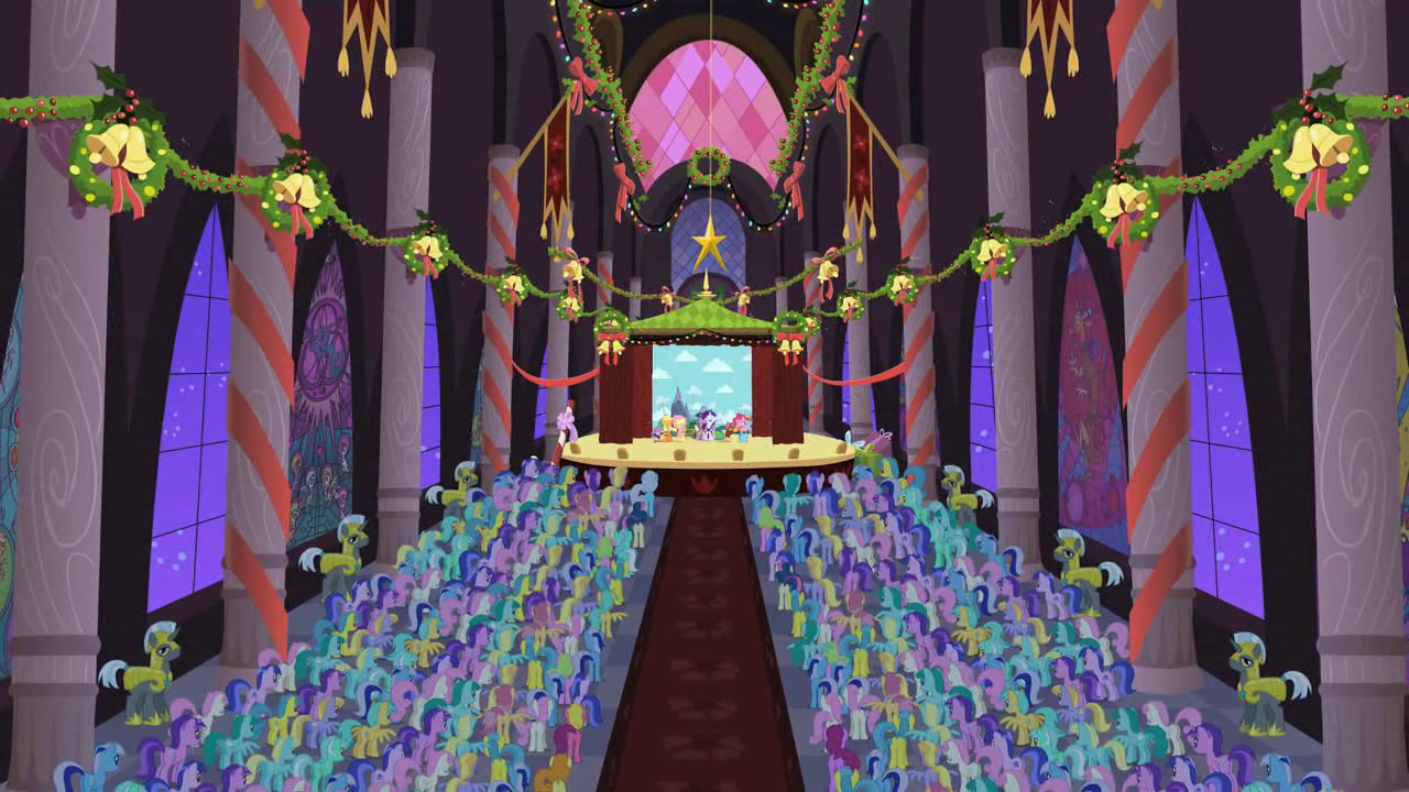 A back-facing shot of hundreds of ponies gathered in front of a stage in a large hall decorated with bells and wreaths. The Mane Six are barely visible on the stage.