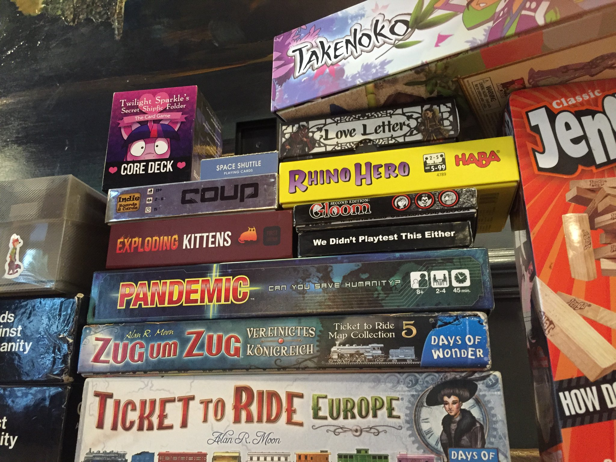 A large pile of tabletop games, including Takenoko, Twilight Sparkle's Secret Shipfic Folder, Love Letter, Coup, Rhino Hero, Gloom, Exploding Kittens, We Didn't Playtest This Either, Pandemic, Ticket to Ride, Jenga, and Cards Against Humanity.