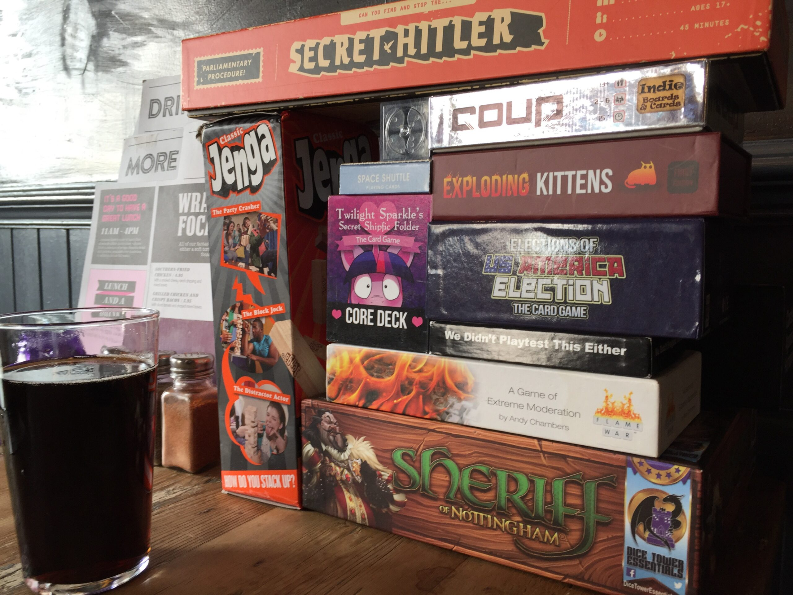 A stack of board games on a table, including Secret Hitler, Coup, Exploding Kittens, Twilight Sparkle's Secret Shipfic Folder, Elections of US America Election: The Card Game, We Didn't Playtest This Either, Flame War, Sheriff of Nottingham, and Jenga. A partially drank pint of cola stands next to the games.