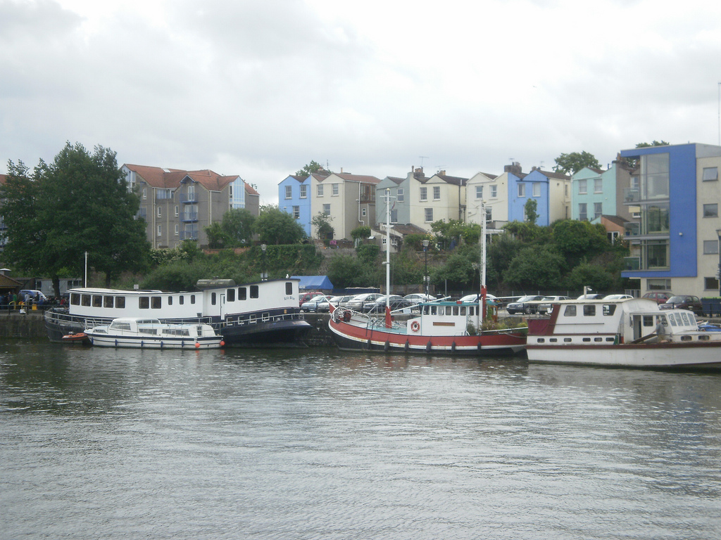 Several large boats parked along the side of a harbour. Tall, narrow, brightly painted houses rise up from behind them.