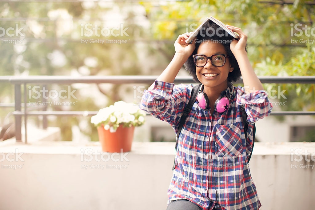 A young black woman wearing glasses, backpack and pink headphones sits outside, smiling and holding a book over her head. The image is covered in iStock/Getty Images watermarks, for the aesthetic.