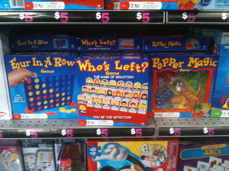 "A shelf of knock-off versions of popular tabletop games, including ""Four in a Row"" (Connect 4), ""Who's Left?"" (Guess Who?), and ""Popper Magic"" (Trouble)."