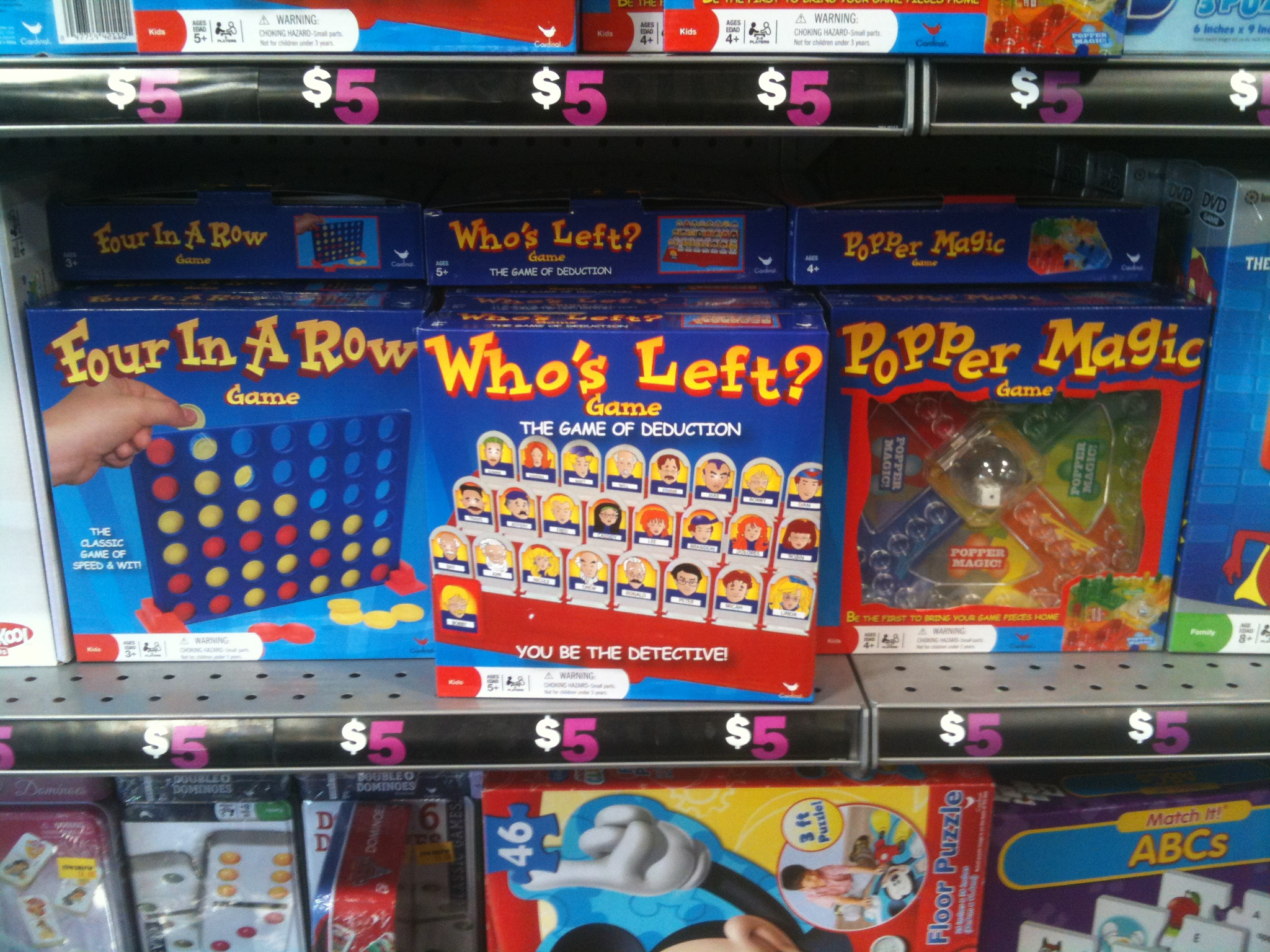 """A shelf of knock-off versions of popular tabletop games, including """"Four in a Row"""" (Connect 4), """"Who's Left?"""" (Guess Who?), and """"Popper Magic"""" (Trouble)."""