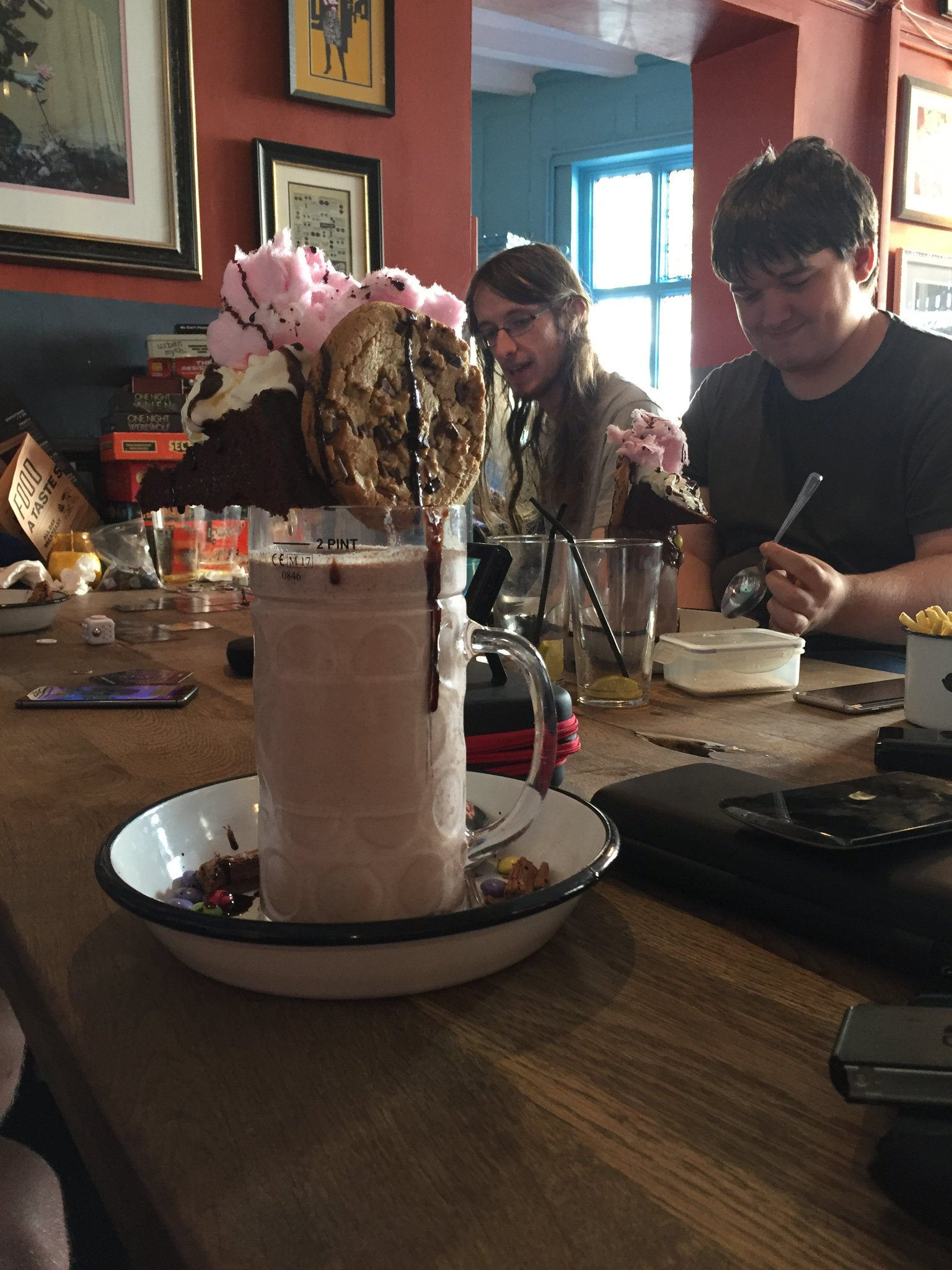 A photo of an insane dessert, composed of a large glass containing two pints of chocolate milkshake, on top of which are balanced a large chocolate chip cookie, a slice of chocolate cake, and a bunch of pink candy floss. The glass is surrounded by Nutella spread and M&Ms, and the entire thing is covered in chocolate sauce.