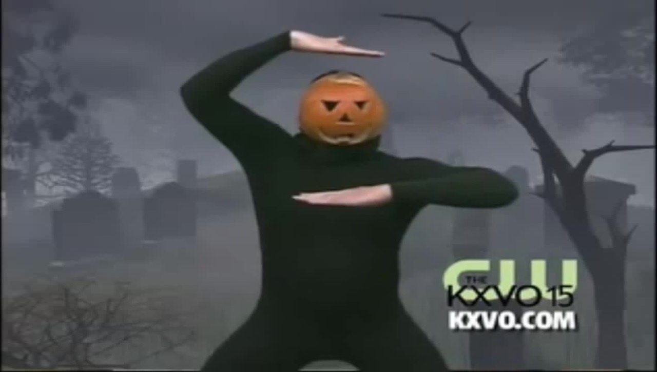 A person dressed in a black bodysuit, with a jack-o'-lantern covering their face, dancing in front of a green screened image of a graveyard.