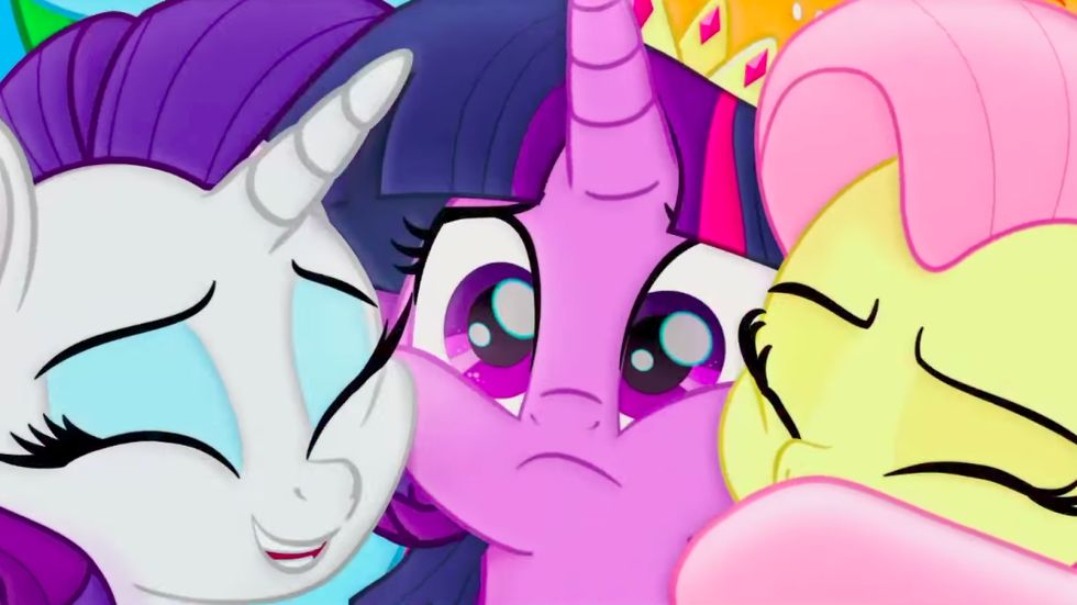 A screenshot from My Little Pony: The Movie. Rarity and Fluttershy happily hug Twilight Sparkle, however Twilight seems to be worried by something.