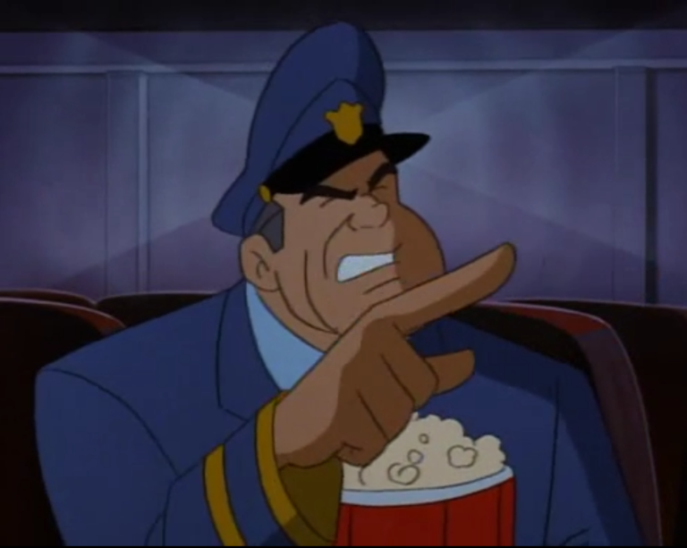 Cosgrove, a burly police sergeant from the cartoon Freakazoid, points accusingly off camera. He holds a bucket of popcorn in his other hand.