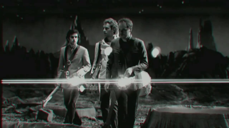 """A black and white still from the music video to Coldplay's """"Talk"""". The band members carry their instruments across the dark surface of an alien planet. Their flashlights leave streaks of lens flare across the image."""