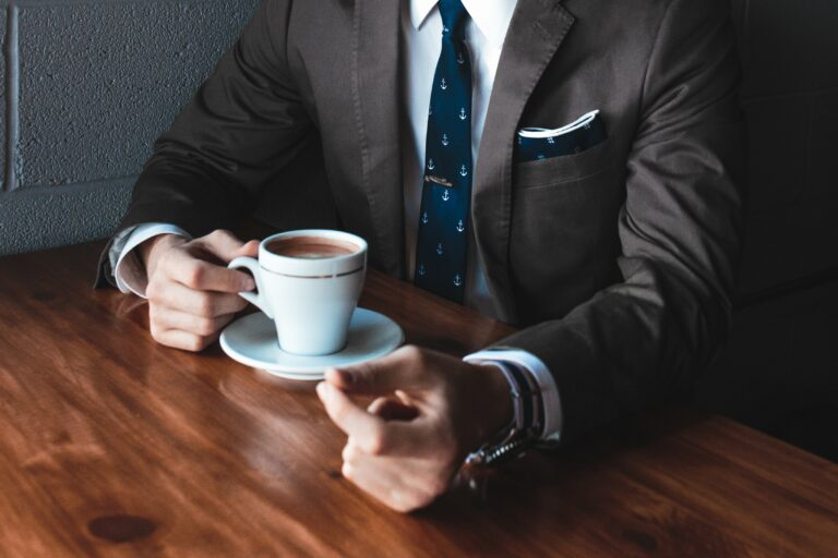 A close up of a man wearing a business suit sat at a table drinking coffee.