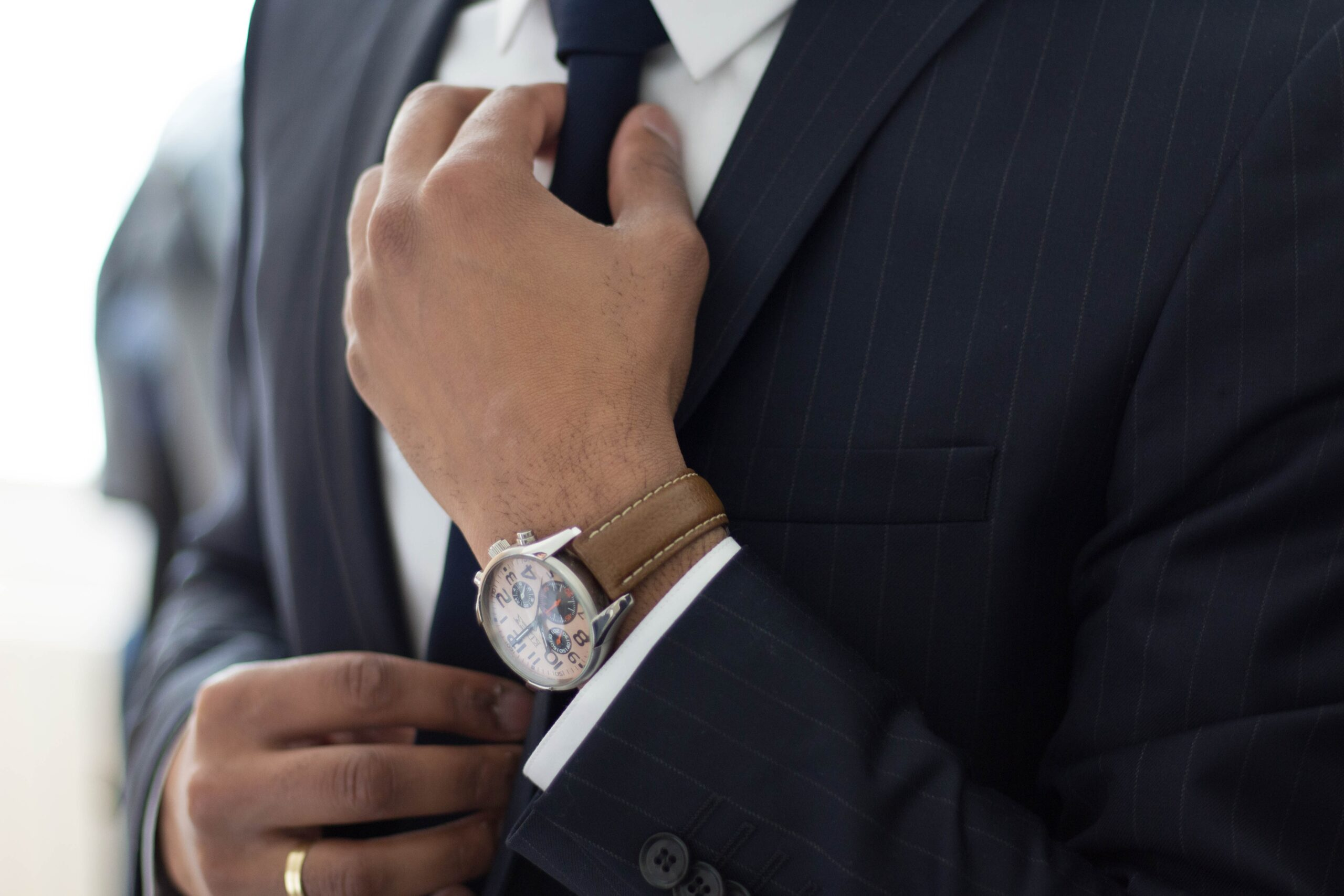 A close up of a man wearing a business suit's upper torso. A gold ring and wristwatch is clearly visible as he adjusts his tie.
