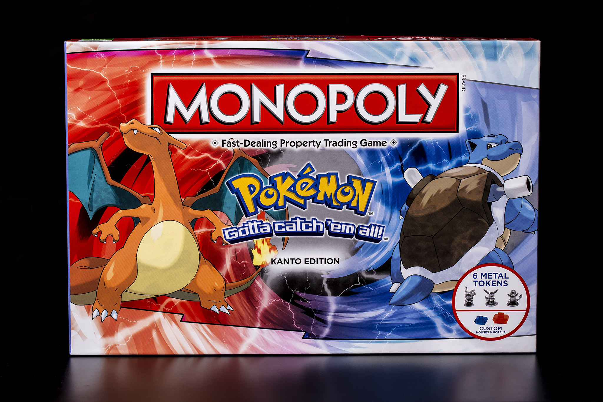 The box front cover for Monopoly Pokémon: Kanto Edition. The cover is half red and half blue, with Charizard and Blastoise depicted in each half.