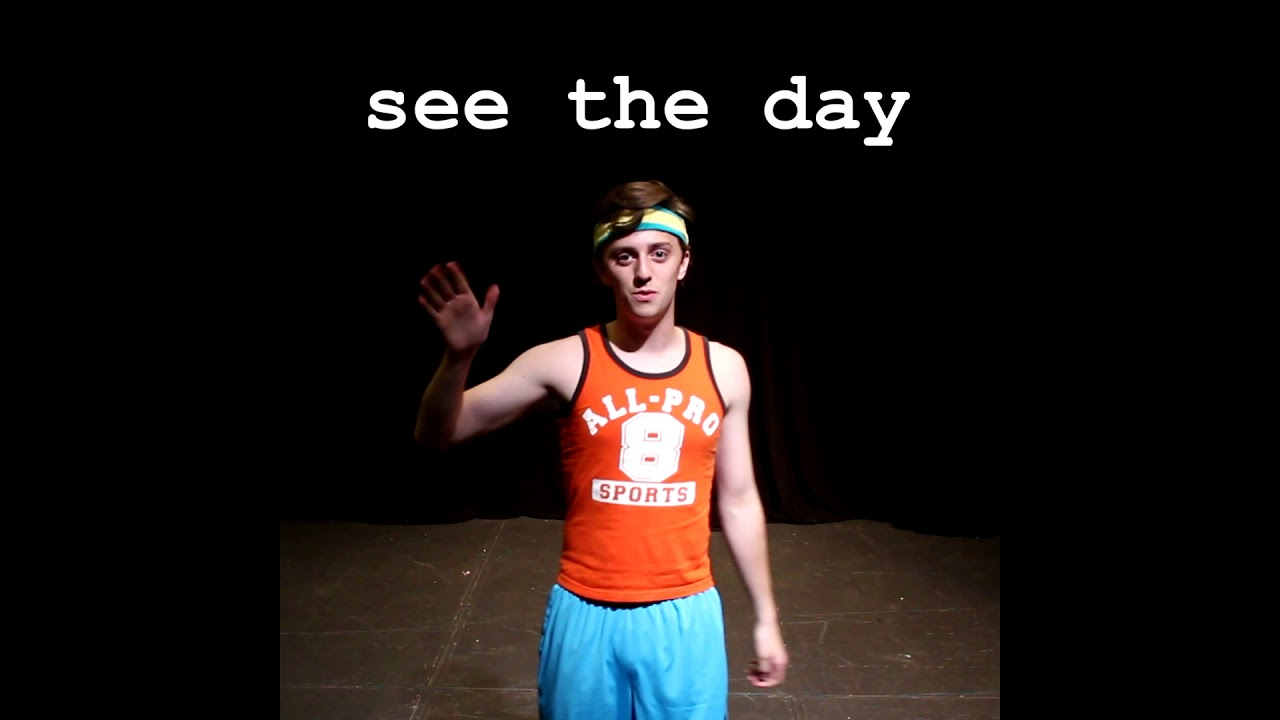 """A photograph of Brian David Gilbert wearing workout clothes, looking and waving at the viewer. The phrase """"see the day"""" is shown above him in large, typewriter-like text."""