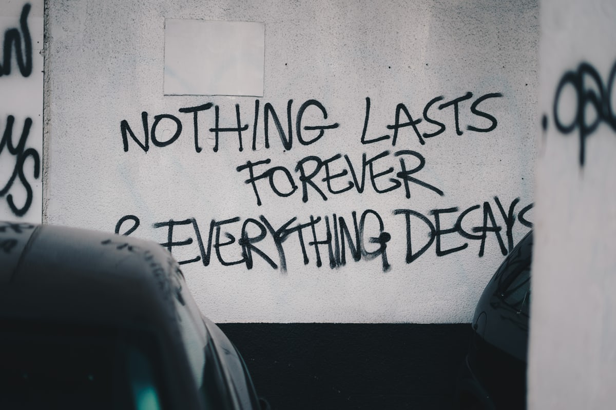 "Graffiti on the wall of a car park, stating ""Nothing lasts forever & everything decays""."