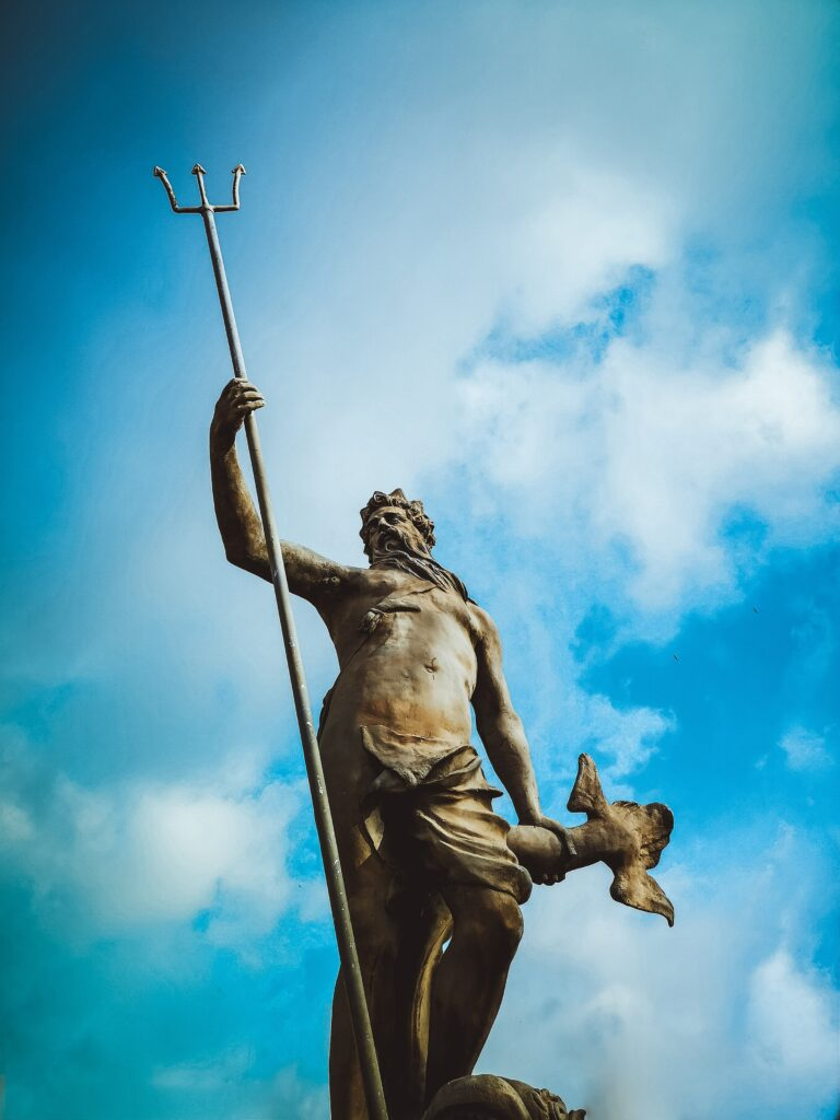 A low-angle photograph of the statue of the Roman god Neptune located in central Bristol, set against a blue, slightly cloudly sky.