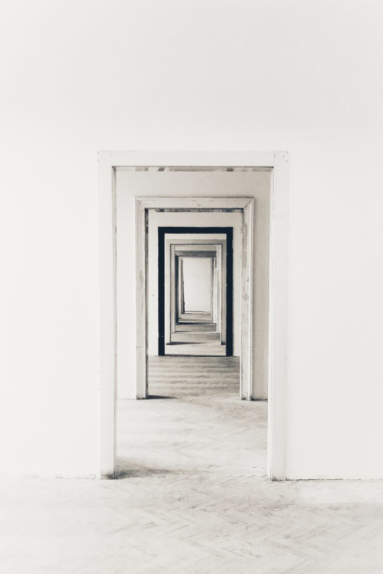 A hallway made up of several doorways, each recurring inside of one another. All of the doorways are white, except for the third, which is black.